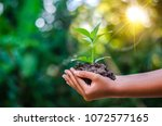 earth day in the hands of trees ... | Shutterstock . vector #1072577165