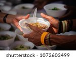 feeding the poor to hands of a... | Shutterstock . vector #1072603499
