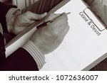 Small photo of A man writes cease and desist in a letter. Black and white photo to illustrate the call to stop actions.