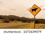 Small photo of Cow Alien Abduction Road Sign along the Turqoise Trail, Route 66 Scenic Byway, in springtime between Santa Fe and Albuquerque, New Mexico.