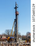 Small photo of pile bore machine. A pile driver is a mechanical device used to drive piles, poles into soil to provide foundation support for buildings