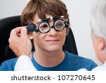 Optometrist taking eye test through trial frames at the clinic - stock photo