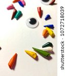 Small photo of Broken tips of colored pencils isolated on white background. Googly, wiggle eyes, face, scattered.