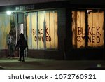 Small photo of Los Angeles, CA/USA; July 16, 2013; People walk past a business on Crenshaw Blvd with the sign 'Black Owned' in the windows. Protests over the Zimmerman acquittal continued in Leimert Park all night.