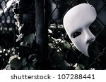 Masquerade - Phantom of the Opera Mask on Rusty Chain Link Fence - stock photo