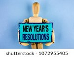 Small photo of Text sign showing New Year'S Resolutions. Conceptual photo Goals Objectives Targets Decisions for next 365 days written Sticky note paper holding by Wooden Robot Toy the plain background.