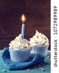 cupcake with a blue candle for... | Shutterstock . vector #1072989989