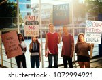 group of teenagers protesting... | Shutterstock . vector #1072994921