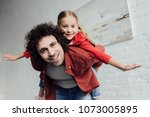 happy father piggybacking cute... | Shutterstock . vector #1073005895