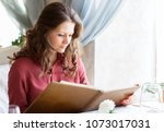 beautiful woman looking at menu ... | Shutterstock . vector #1073017031
