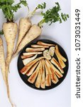 Small photo of Parsnip. Fresh parsnip. Pasher with parsley against white background. A few fresh parsnips with parsley. Petrushevye grass. Fresh vegetable.