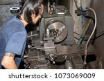 man working on a lathe not wear ... | Shutterstock . vector #1073069009