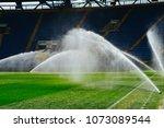 Irrigation turf. Sprinkler watering football field. System working on fresh green grass on football or soccer stadium. - stock photo