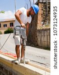 bricklayer building a new wall... | Shutterstock . vector #1073124935