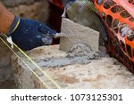 bricklayer making a new wall | Shutterstock . vector #1073125301