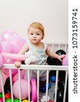 Small photo of Little cute baby girl princess jumps on a bed and playing with colored air balloons. having fun, grabbing. Family, new life, childhood, beginning concept, learning grab. Studio. Close up.