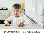 child sits at the table and... | Shutterstock . vector #1073178239