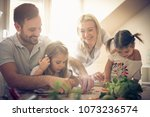 happy young family preparing... | Shutterstock . vector #1073236574