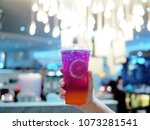 Small photo of Holds a plastic glass of iced tea with clear boba layer colorful of grapefruit, lemon and butterfly pea juice. Selective focus.
