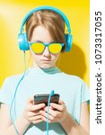 Small photo of Teenager with ponytail wearing sunglasses and blue headphones listening to music with smartphone on yellow backdrop
