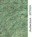 This is a close-up background texture shot of a greenish rock wall. - stock photo