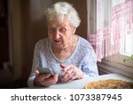 elderly woman sits with a... | Shutterstock . vector #1073387945
