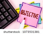 Small photo of Text sign showing Objective. Conceptual photo Goal planned to be achieved Desired target Company mission written on Pink Sticky Note paper on plain background Marker and Black Keyboard.