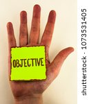 Small photo of Handwriting text writing Objective. Concept meaning Goal planned to be achieved Desired target Company mission written on Sticky Note Paper placed on Hand on the plain background.