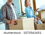couple unpacking cardboard... | Shutterstock . vector #1073561651