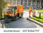 Sweeper machine in the process of cleaning the street. А man in uniform cleans the street. Street cleaning. Municipal service cleans the city.