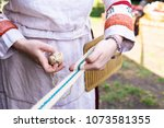 Small photo of Shallow focus. Traditional Viking or Slavic belt or trim. Woman weaving patterned bands with a double holed heddle. Old craft, method of producing narrow straps. Viking age or medieval techniques.