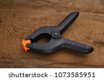 black plastic clamp on a wood... | Shutterstock . vector #1073585951