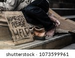 Small photo of homeless begging man's hand with money in his hat on the street