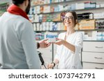 young woman pharmacist giving...   Shutterstock . vector #1073742791