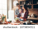 husband kissing wife on kitchen ... | Shutterstock . vector #1073854511
