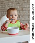 happy baby with a spoon and... | Shutterstock . vector #1073867045