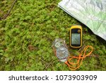Small photo of finding the right position in the forest with a compass, map and GPS
