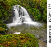Small photo of Waterfall falling in a lake with abundant water and a stone cover by moss