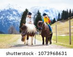 kids riding pony in the alps... | Shutterstock . vector #1073968631