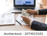 business man  holding money us... | Shutterstock . vector #1074015101