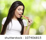 young woman eating a piece of... | Shutterstock . vector #107406815