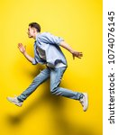 young handsome man jumping on... | Shutterstock . vector #1074076145