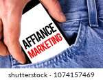 Small photo of Conceptual hand writing showing Affiance Marketing. Business photo showcasing joining two or more companies in same field mutual goal written on Mobile phone holding by man the Jeans background.