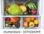 open fridge full of vegetables... | Shutterstock . vector #1074264395