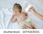 mother pouring talcum powder to ... | Shutterstock . vector #1074265031