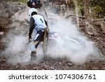 Small photo of Accident in mountain bikes race in dirt track with flying debris during an acceleration. Concept of focus between an accelerate in action sport