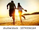 happy couple running to the sea ... | Shutterstock . vector #1074336164