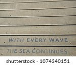 Small photo of The Sea Poem engrave in a wooden deck outdoors
