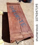 Small photo of Box of dynamite sand desert old red text sign vintage wood outdoors summer west wild