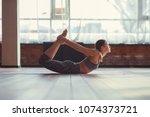 active woman practicing yoga in ... | Shutterstock . vector #1074373721